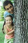 Girl and father peeking around tree Stock Photo - Premium Royalty-Free, Artist: Siephoto, Code: 695-05765937