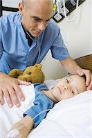sad girls - Girl lying in hospital bed, male nurse's hand on girl's forehead Stock Photo - Premium Royalty-Freenull, Code: 695-05765990