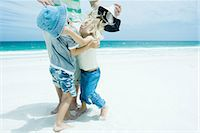 Family on beach, boy and girl reaching for each other in front of father Stock Photo - Premium Royalty-Freenull, Code: 695-05766154
