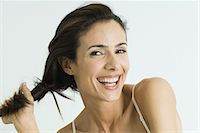 Woman twisting hair to the side, smiling at camera, portrait Stock Photo - Premium Royalty-Freenull, Code: 695-05766195