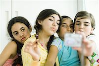 preteen kissing - Young female friends with make-up looking at selves in hand mirror Stock Photo - Premium Royalty-Freenull, Code: 695-05766231