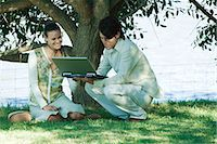 sitting under tree - Couple under tree, man holding open laptop Stock Photo - Premium Royalty-Freenull, Code: 695-05766335