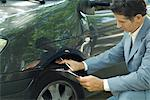 Mature man in suit inspecting car Stock Photo - Premium Royalty-Freenull, Code: 695-05766450