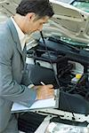 Mature man in suit inspecting car Stock Photo - Premium Royalty-Free, Artist: Science Faction, Code: 695-05766453