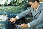Mature man in suit inspecting car Stock Photo - Premium Royalty-Freenull, Code: 695-05766455