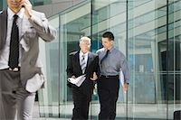 Two businessmen walking together, discussing, building in background Stock Photo - Premium Royalty-Freenull, Code: 695-05766526