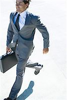 Young businessman running outdoors, carrying briefcase Stock Photo - Premium Royalty-Freenull, Code: 695-05766573