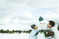 preteen kissing - Three young friends kissing snowman, head and shoulders Stock Photo - Premium Royalty-Freenull, Code: 695-05766599