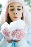 Preteen girl holding handful of snow in mittens, blowing Stock Photo - Premium Royalty-Freenull, Code: 695-05766620