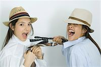 Two young female friends dressed in hats, pulling each other's ties, laughing at camera Stock Photo - Premium Royalty-Freenull, Code: 695-05766853