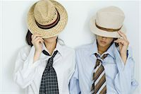 Two young friends pulling hats down over their faces, portrait Stock Photo - Premium Royalty-Freenull, Code: 695-05766856