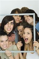 Young friends holding up frame together, smiling at camera Stock Photo - Premium Royalty-Freenull, Code: 695-05766865