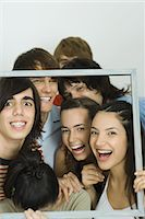 Young friends holding up frame together, smiling at camera Stock Photo - Premium Royalty-Freenull, Code: 695-05766866