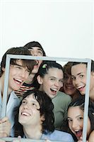 Group of young friends posing for photo, holding up picture frame, laughing, portrait Stock Photo - Premium Royalty-Freenull, Code: 695-05766967
