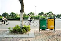 China, Guangdong Province, Guangzhou, cyclists riding in street behind recycling bins Stock Photo - Premium Royalty-Freenull, Code: 695-05767131