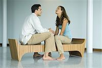 Young couple sitting face to face on bench, laughing together Stock Photo - Premium Royalty-Freenull, Code: 695-05767410