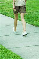 Female walking on sidewalk, waist down, rear view Stock Photo - Premium Royalty-Freenull, Code: 695-05767509