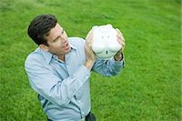 Man holding piggy bank upside down, looking surprised Stock Photo - Premium Royalty-Freenull, Code: 695-05767543