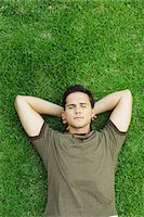 Young man lying on grass with hands behind head, eyes closed, high angle view Stock Photo - Premium Royalty-Freenull, Code: 695-05767786
