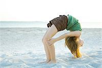 preteen girls gymnastics - Little girl doing backbend at the beach, side view Stock Photo - Premium Royalty-Freenull, Code: 695-05767833