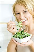 sprout - Woman eating radish sprouts with chopsticks, smiling at camera Stock Photo - Premium Royalty-Freenull, Code: 695-05767865