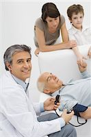 Doctor measuring patient's blood pressure, smiling over shoulder at camera, patient's family in background Stock Photo - Premium Royalty-Freenull, Code: 695-05767897