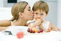 people kissing little boys - Woman kissing little boy on cheek, boy eating apple Stock Photo - Premium Royalty-Freenull, Code: 695-05767940