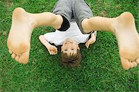 Boy lying on grass with legs in air, overhead view Stock Photo - Premium Royalty-Freenull, Code: 695-05768146