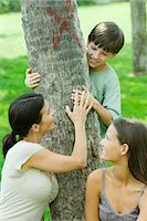 Mother and son embracing tree, teen daughter smiling over shoulder at them Stock Photo - Premium Royalty-Freenull, Code: 695-05768180