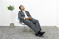 Businessman relaxing in rock garden, listening to mp3 player Stock Photo - Premium Royalty-Freenull, Code: 695-05768251