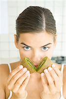 smelly - Woman holding halves of kiwi to her nose, looking at camera Stock Photo - Premium Royalty-Freenull, Code: 695-05768501