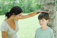 preteen touch - Mother measuring son's height on tree trunk Stock Photo - Premium Royalty-Freenull, Code: 695-05768564