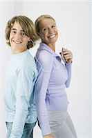 Mother and teen son listening to MP3 player together, standing back to back, smiling at camera Stock Photo - Premium Royalty-Freenull, Code: 695-05768848