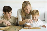 Family playing board game together Stock Photo - Premium Royalty-Freenull, Code: 695-05768885