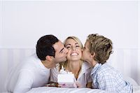 Woman holding a gift, husband and son kissing her on both cheeks Stock Photo - Premium Royalty-Freenull, Code: 695-05769105
