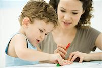 Mother and son sitting together, coloring with crayons Stock Photo - Premium Royalty-Freenull, Code: 695-05769245