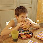 Boy eating hamburger Stock Photo - Premium Royalty-Free, Artist: iRepublic, Code: 695-05769339