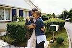 Couple standing in front of house, embracing Stock Photo - Premium Royalty-Free, Artist: Robert Harding Images, Code: 695-05769699