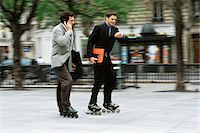 roller skate - Men in business attire rollerskating together along sidewalk, one phoning, the other looking at watch Stock Photo - Premium Royalty-Freenull, Code: 695-05769981