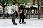 Men in business attire rollerskating together along sidewalk, one phoning, the other looking at watch Stock Photo - Premium Royalty-Free, Artist: Photocuisine, Code: 695-05769981