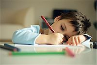Little boy resting head on arm, drawing with colored pencils Stock Photo - Premium Royalty-Freenull, Code: 695-05770152
