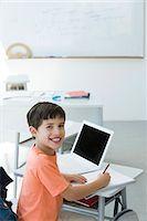 Elementary school student doing classwork, smiling at camera Stock Photo - Premium Royalty-Freenull, Code: 695-05770533
