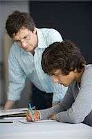 College student working on assignment, teacher assisting Stock Photo - Premium Royalty-Freenull, Code: 695-05770806