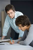 Teacher leaning on desk assisting student in classroom Stock Photo - Premium Royalty-Freenull, Code: 695-05770807