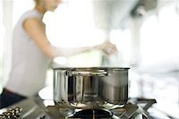 stove - Pot cooking on stove, woman in background Stock Photo - Premium Royalty-Freenull, Code: 695-05770931