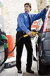Well-dressed man refueling vehicle at gas station Stock Photo - Premium Royalty-Free, Artist: Cultura RM, Code: 695-05771076