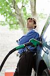 Well-dressed man refueling vehicle at gas station Stock Photo - Premium Royalty-Free, Artist: Simon Katzer, Code: 695-05771079