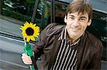 Man at gas station holding gas nozzle with sunflower emerging from end Stock Photo - Premium Royalty-Free, Artist: Transtock, Code: 695-05771085