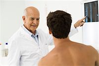 Doctor explaining x-ray to patient Stock Photo - Premium Royalty-Freenull, Code: 695-05771246