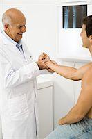 Doctor examining patient's wrist Stock Photo - Premium Royalty-Freenull, Code: 695-05771247